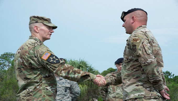 U.S. Army Command Sgt. Maj. John W. Troxell, senior enlisted advisor to the chairman of the Joint Chiefs of Staff, presents a coin to Tech. Sgt. Matthew McElyea, 6th Security Forces Squadron kennel master, July 11, 2019, at MacDill Air Force Base, Fla.