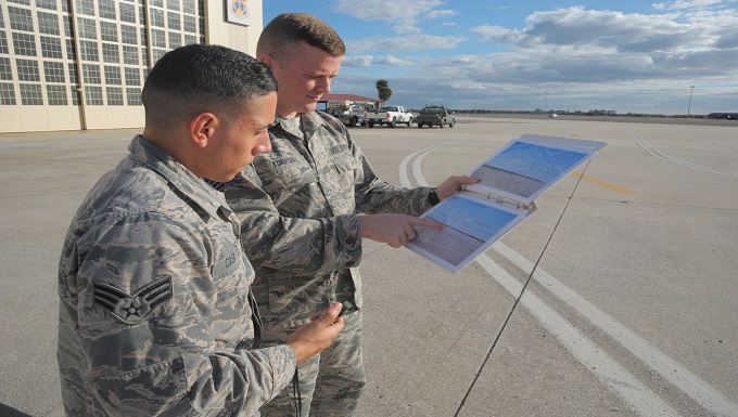 Senior Airman Jonathan Casillas, left, and Staff Sgt. Shane Yurkus, right, both weather forecasters with the 6th Operations Support Squadron, review a visibility binder at MacDill Air Force Base, Fla., Jan. 11, 2017. The binder includes an image with measurements of distance to specific landmarks on the flightline which are used to manually calculate visibility during foggy weather. (U.S. Air Force photo by Airman 1st Class Adam R. Shanks)