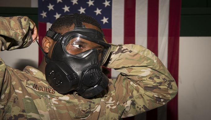 Airman 1st Class Kerson Jacques, a 6th Communications Squadron radio transmission systems technician, puts on a gas mask during deployment readiness training at MacDill Air Force Base, Fla., July 25, 2019. More than 230 members of the 6th Mission Support Group participated in a two-day readiness exercise to learn about important survival skills to succeed in a deployed environment.  (U.S. Air Force photo by Senior Airman Scott Warner)