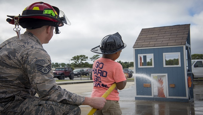 A 6th Civil Engineer Squadron Fire Emergency Services Flight firefighter teaches a Tinker Elementary student how to operate a fire hose during Fire Prevention Week at MacDill Air Force Base, Fla., Oct. 8, 2019. Fire Prevention Week's purpose is to educate the community about the importance of planning and using good fire safety practices. (U.S. Air Force photo by Senior Airman Scott Warner)