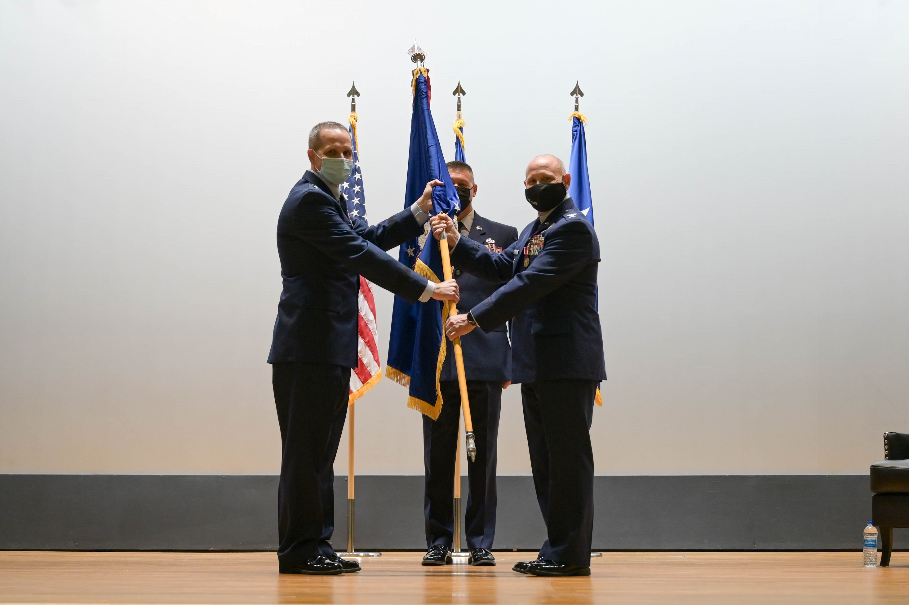 Maj. General Jeffrey T. Pennington, 4th Air Force commander, passes the guidon to Col. Kurt A. Matthews as he takes command of the 927th Air Refueling Wing during a ceremony Sept. 11, 2021 in the base theater at MacDill Air Force Base, Florida.